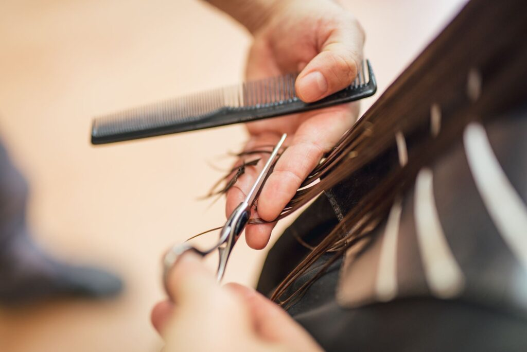 Close-up of a  man hairdresser cutting the hair of a woman.